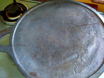 Cast iron tava after applying oil for seasoning